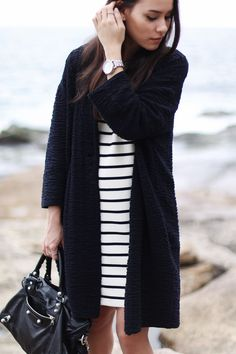 Nisi is wearing: Balenciaga Giant 12 City Bag, striped dress and an egg-shaped cardigan at Bondi Beach