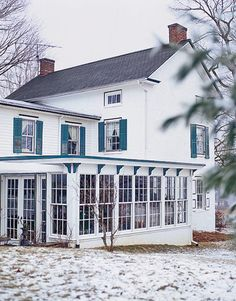 white two story house with blue shutters and details