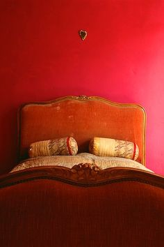 Saturated color, deep pinky red walls, rusty orange velvet antique bed head dressed with Indian pillow rolls. Charming bedroom bohemian eclectic. Love to do this in greens and blues