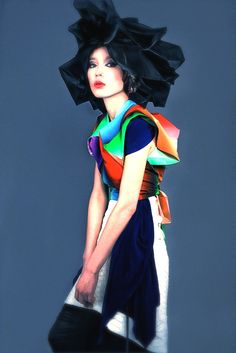 Origami shirt by 132 5. Issey Miyake; Blue shawl, scale skirt and black skirt by Somarta; Skirt (on head) by Saphir East