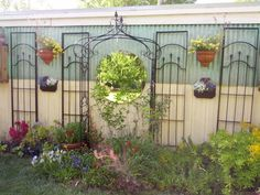 """Upcycled gazebo panels & old vanity mirror adorn ugly wall., I used everything I could find to cover this ugly tool shed wall. My dad built the planter """"boxes"""". The gazebo panels were painted black, added the mirror and many plants including bouganvilla, mandevilla, gazanias, roses, sunflowers, lilacs, etc., Gardens Design"""