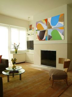 Fire and Art    This modern fireplace omits the mantel, which enhances the effect of the bright, abstract paintings above it. The furniture and area rug are kept neutral to maintain the color balance in the space