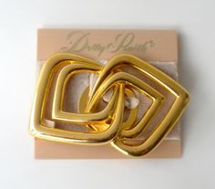 This is a gold tone chrome finish geometric interlocking square shaped belt buckle by Dotty Smith. On original card.  Measures: 2.75 inches