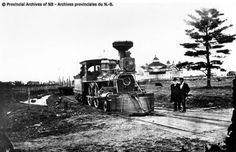 """engine of the Fredericton Branch Railway at York St. Men standing at the crossing are Alexander """"Boss"""" Gibson and Fred B.Edgecombe, Station Agent at Fredericton. TAYLOR, GEORGE: PHOTOGRAPHS, Provincial Archives of New Brunswick New Brunswick, Engine, Archive, Boss, Photographs, History, Men, Motor Engine, Photos"""