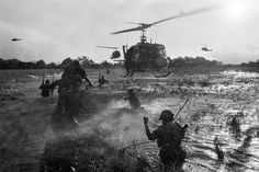 """As U.S. """"Eagle Flight"""" helicopters hover overhead, South Vietnamese troops wade through a rice paddy in Long An province during operations against Viet Cong guerrillas in the Mekong Delta, December 1964. The """"Eagle Flight"""" choppers were loaded with Vietnamese airborne troops who were dropped in to support ground forces at the first sign of enemy contact"""