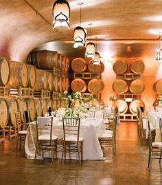 Romantic reception in a winery barrel room with ivory accents, gold Chiavari chairs and amber-colored up-lighting