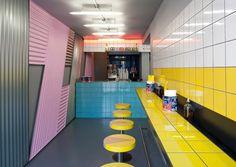 LONDON: NACHTCLUBBESITZER ERÖFFNEN NEON-PIZZERIA  Zwischen geometrischen Mustern, 80er- Jahre-Grafik und bunten Fliesen ordern Gäste ausschließlich stückweise von der riesigen New York Style-Pizza, die einen Durchmesser von 140 Zentimetern hat.
