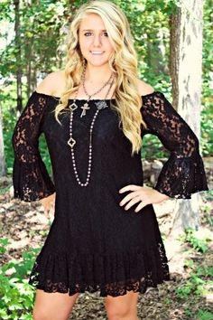 Black lace dress with bell sleeves & ruffle at the bottom.