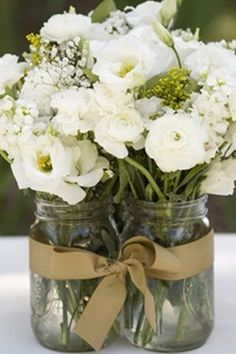 Burlap + Lace Centerpiece Effortless white flowers like hydrangea and baby's breath can be arranged in a mason jar wrapped in twice and lace for a simple and inexpensive centerpiece.