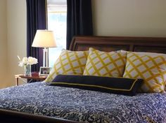 I really enjoy the color scheme of rich wood, cream, deep navy, and yellow. I like the bedspread and the lamp, as well as the pillows.  Navy Master Bedroom with Gold Accents traditional-bedroom
