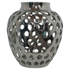 Ceramic vase with a silver finish and circle cut-outs.   Product: VaseConstruction Material: CeramicC...