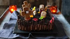 Kids will love picking off the sweets and biscuits from this fun #Halloween graveyard cake, complete with biscuit tombstones.