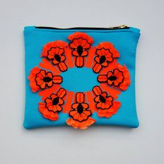 TURQUOISE CLUTCH PURSE with a fluorescent orange vinyl print and 3d, textured jewel detail.