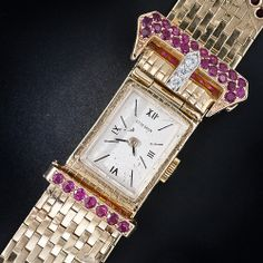 Retro Buckle Bracelet Watch with Rubies and Diamonds,This classic Retro period buckle bracelet glistening with rubies and diamonds cleverly conceals a seventeen jewel timepiece by the highly respected Swiss watchmakers - M & W Ullman. Just flip-up the end of the belt and voilà - it's cocktail time! The dial is signed Otto Grun.