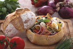 L'insalatona nel pane è ideale per i pic nic: verdure estive, mozzarella, tonno, olive, uova sode presentate in una fragrante crosta di pane pugliese