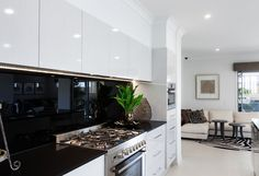 caeserstone jet black benchtop, with masters charcoal splashback, - white gloss no handle overhead cabnets