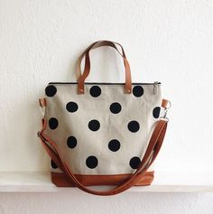 This crossbody bag is made of natural canvas with handprinted large polka dots. The bottom and the long strap are made of faux vegan leather in tan toffee color and the handles are made of genuine leather for extra support. It is lined with cotton in cinnamon brown color. * Two slip pockets