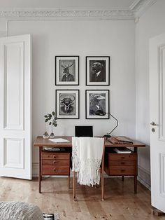 vintage desk with drawers, monochrome art, white throw, black lamp, wooden floors