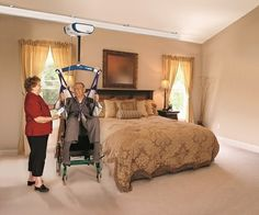 The Voyager Duo ceiling lift. Shown here on a straight track for safe and secure access from wheelchair to bed.