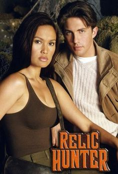 """Relic Hunter(1999)_ Sydney Fox is a professor but primarily a globe-trotting """"relic hunter,"""" looking for ancient artifacts to return to museums &/or the ancestors of the original owner. She's aided by her linguistic assistant Nigel, & occasionally by her somewhat air-headed secretary Claudia. She often ends up battling rival hunters seeking out artifacts for the money."""