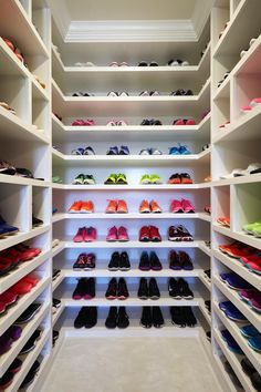 This sneaker display is as impressive as the collection is fabulous. Custom L-shaped shelves utilize corners to get the most of the narrow space for the stunning focal point of this contemporary walk-in closet.