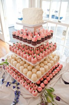 Lovely cupcake tower with coral and white wedding cupcakes plus a white cake on top for the slicing! Love this idea, just diff colors. #WeddingIdeasForKids