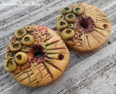 Material: Polymer clay  Process: handmolded, carved, fired, cured, sanded and sealed  Colors: muted caramel, green and rustic red  Hole