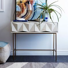 Gorgeously geometrical. With its strikingly modern drawer fronts hewn from powder-coated brushed metal and laid atop antique brass-finished legs, our Sculpted Geo Console's architectural shape is balanced by its soft colour palette. Ideal for entryways, it's equipped with two deep drawers for stashing keys, mail and more.