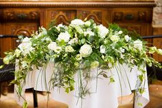 Long and low top table arrangement shape can also be used on alter in church. By http://www.twistedwillowfloristry.co.uk.