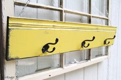 "This one of a kind wall rack is made from reclaimed wood, painted yellow and distressed with black accents and the natural wood. It measures 6"" x 35 1/2"", comes ready to hang on the wall, and has 3 sturdy triple black hooks perfect for hats, jackets, umbrellas, or jewelry."