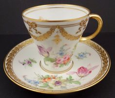 $295 This porcelain tea cup and saucer was produced in Germany at the Donath Dresden studio in the 1890s. The saucer has a diameter of 5 1/4 inches and the cup is 2 3/4 inches high. Note the elegant shape of the cup and graceful handle. The set is hand decorated with sprays of vibrantly colored flowers. There are accents of garlands, ribbons and border trim with raised gold and gold beads. Inside the cup are raised gold sprigs.