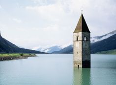 The flooded tower of a century church rises from Lago di. The flooded tower of a century church rises from Lago… Lago Powell, 14th Century, Beautiful World, Places To Go, Tower, Mountains, City, Nature, Bella