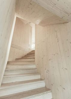 An enclosed wooden staircase that wraps around one of the corners of this house in Austria leads down to a basement and up to the first floor, which contains the main office, a lounge area and a kitchen