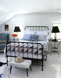 Black iron bed and blue/white quilt. Pottery Barn game board side table as a nightstand.