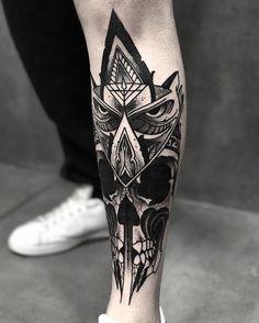Tatuagem na canela de uma coruja com olhar zangado e uma caveira logo abaixo onde supostamente seria seu peito.