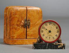 Brevet Art Deco Travel Alarm Clock  Boxed gilt-brass, enamel, and marble  Switzerland, second quarter 20th century  Red enameled brass bezel, engine-turned dial, gilt-metal rose blossom supports on a rectangular black marble base.