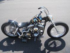 shovelhead swingarm custom with spool front wheel and ribbon paint job.