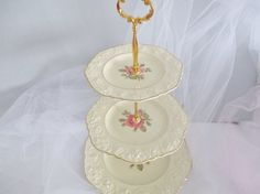 A beautiful off white 1930s Crown Ducal 3-tier cake stand or tea stand. Antique raised border motif with single pink rose centre. Soft creamy