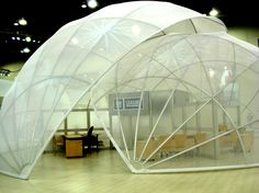 """Mesh Domes - they are terrific spaces.  These 2 overlapping domes were constructed from 2"""" round tubing and covered in miller mesh material that provided the look of subtle privacy. The edge finishing around the perimeter of each dome was constructed using a spandex zipper pocket."""
