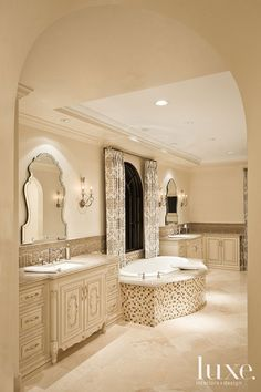 Sandy-toned mosaic tiling from Facings of America dresses the master bathroom's tub, which sits between custom- finished alder wood vanities...