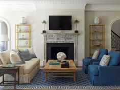 Beautiful living room with ivory slipcovered sofa paired with blue pillows, blue slipcovered chairs paired with ivory pillows and re-claimed wood coffee table over blue trellis with Greek key border.