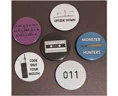Hand-made metal pin-back badges / magnets Size: 59mm Please specify which badge you would like in the drop down menu. You can choose from: - Upside Down - Mixtape - Monster Hunters - 011 - Code Shut Your Mouth - Alphabet purple - 3 Badges (If you choose this option, there is a