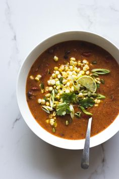 Vegan roasted tomato soup with black beans and polenta. Topped with sweet corn salsa, cilantro, lime and toasted pumpkin seeds.