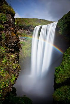 Mist from the powerful Skogafoss waterfall combined with sunlight creates a spectacular rainbow.