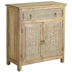 Exquisitely grained mango-wood cabinet with henna-style carvings, artfully whitewashed to show the intricate detail. Antique brass pulls on the top drawer and two lower doors. The Henna cabinet from Pier1.