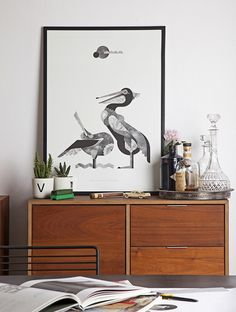 A simple mid-century sideboard holds a bar & acts as a place to rest your favorite artwork. Very cool...V
