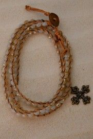 Czech crystals are sewn between tan leather to wrap multiple times around your wrist on this lustrous bracelet. The piece has three sizing options with a copper button closure. The decorative cross charm is cast bronze and is the finishing touch. #Christian #bling #wrapbracelet #cross #jewelry