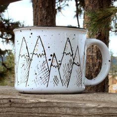 This cute 13oz mug looks just like an enamel camp mug, but its really made out of durable ceramic! Hand painted with a mountain range at sunrise, its