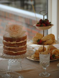 Summer wedding dessert table. Naked vanilla cake with strawberries and cream filling. Scones with strawberries & cream displayed with vintage glassware. Baked by the Handmade Cake Company