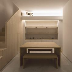 A workspace for the client, a graphic designer, is set on the ground floor of this house by Do Do, where a white shelf at the top of the room forms an elevated walkway for the cat. It leads to a square opening in the staircase banister – allowing the cat to pop in and out.